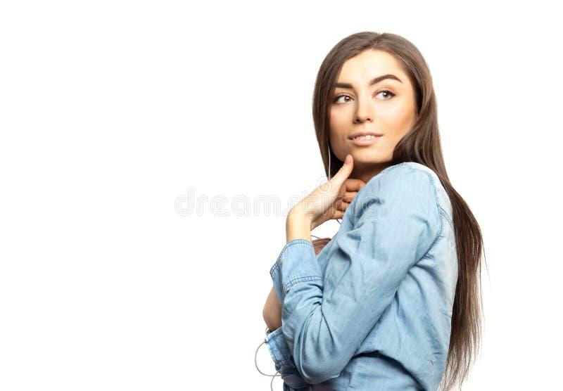 Портрет молодой женщины брюнет слушая к музыке при наушники рассматривая ее плечо стоковые фото