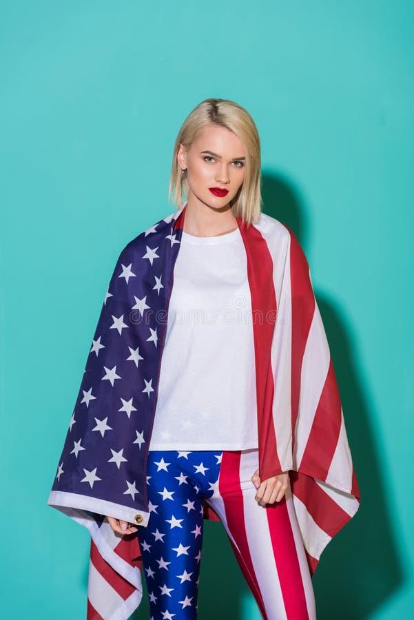 портрет молодой женщины в белой рубашке с американским флагом на голубом фоне празднуя 4-ое стоковое фото