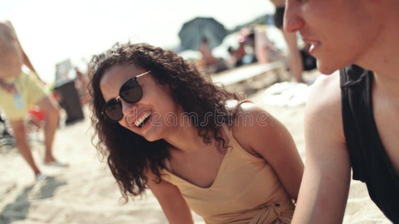 Портрет молодой женщины в бикини сидя с друзьями на пляже и усмехаться стоковые фотографии rf