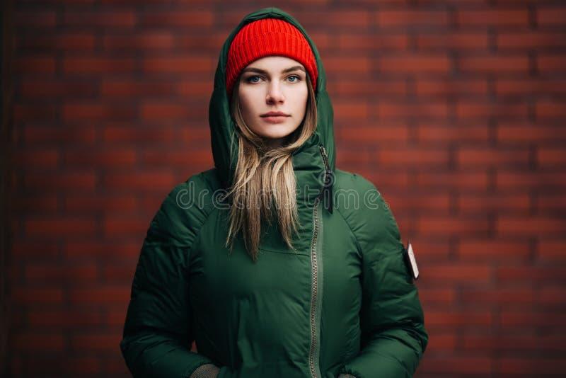 Портрет молодой женщины в зеленой куртке и красной шляпе на предпосылке кирпичной стены стоковые изображения rf