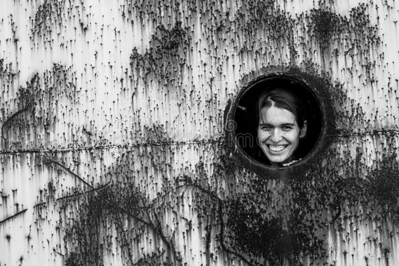 Портрет молодой женщины в круглом окне в ржавой железной стене стоковое фото rf