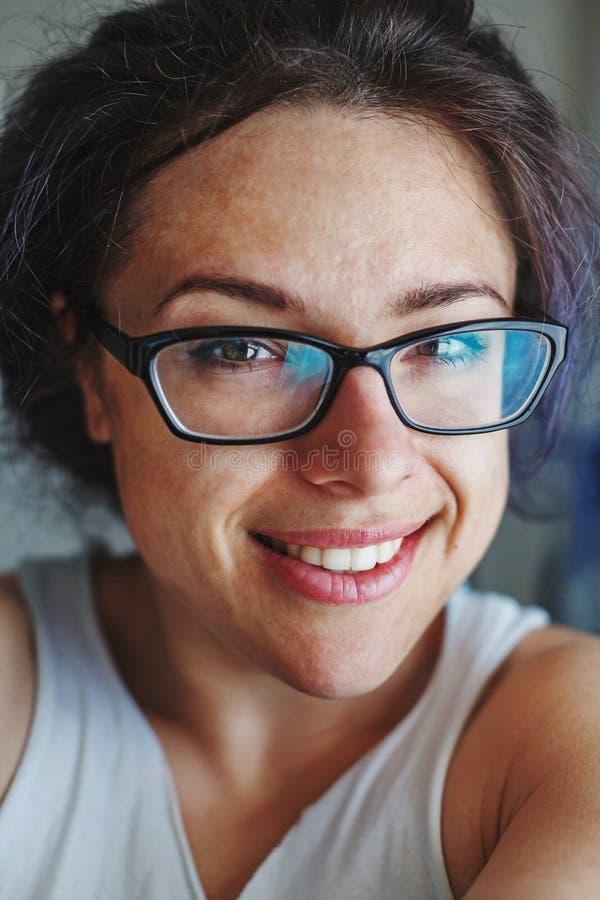 Портрет молодой женщины в черноте обрамил усмехаться стекел стоковое изображение