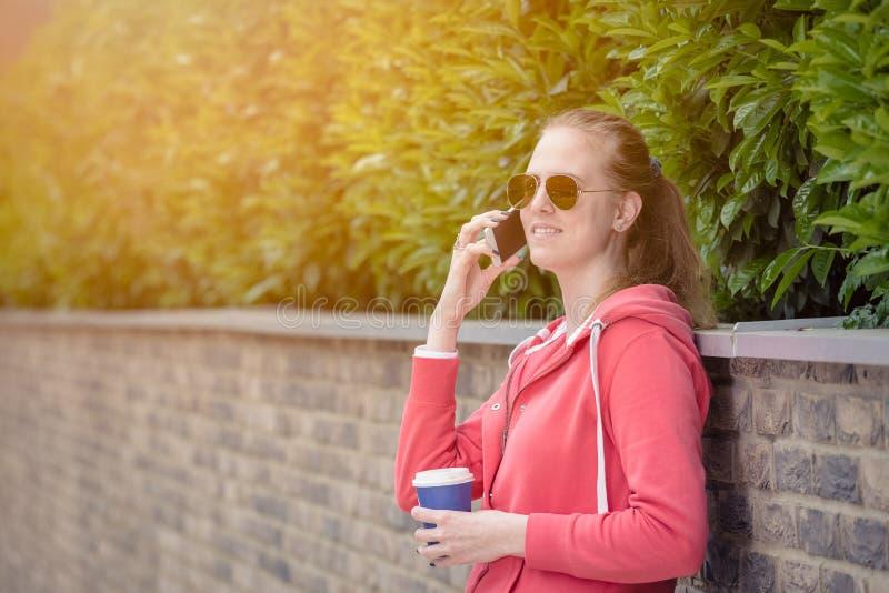 Портрет молодой женщины звоня путем использование smartphone и h стоковое изображение