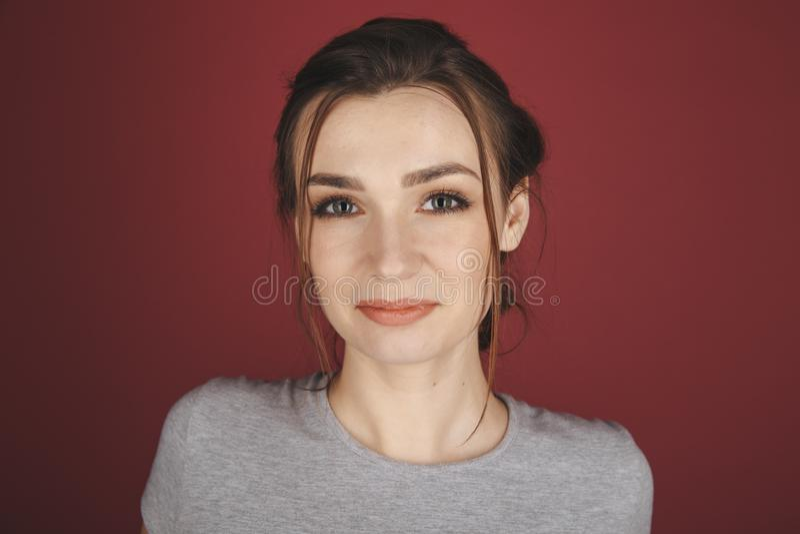Портрет молодой женщины представляя изолированный над красной предпосылкой стоковая фотография