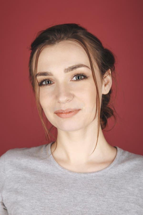 Портрет молодой женщины представляя изолированный над красной предпосылкой стоковые изображения rf