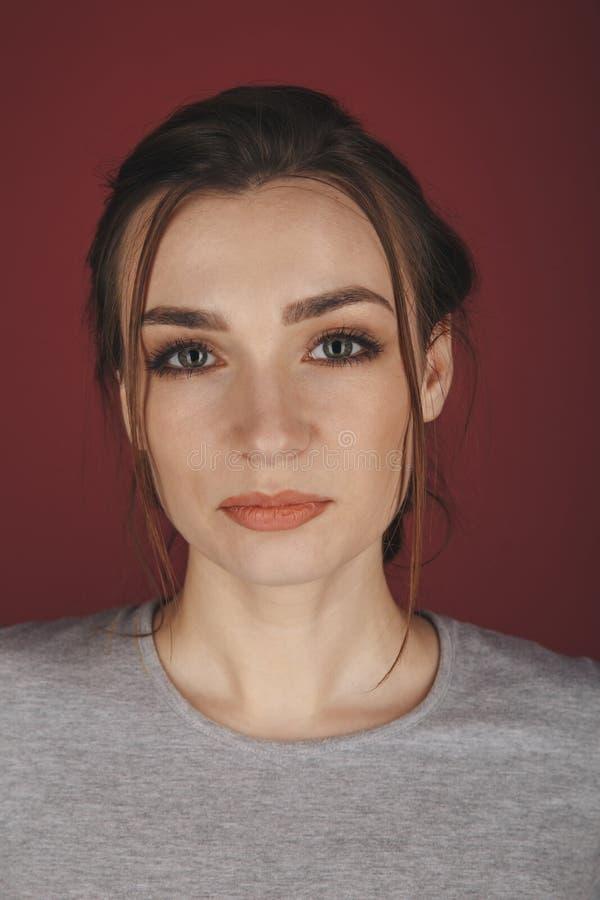 Портрет молодой женщины представляя изолированный над красной предпосылкой стоковое изображение