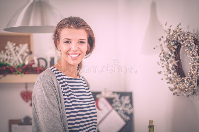 Портрет молодой женщины против предпосылки интерьера кухни стоковое изображение