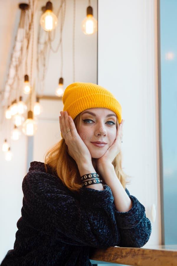 Портрет молодой женщины с голубыми глазами и светлыми волосами в желтой вязать шляпе в кафе стоковая фотография rf