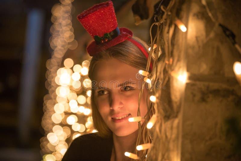 Портрет молодой женщины с украшением рождества освещает стоковые фото