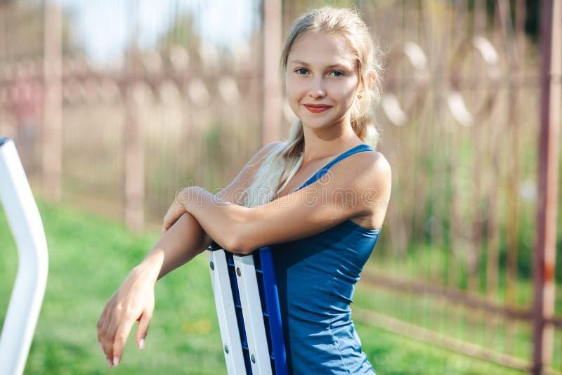 Портрет молодой женщины фитнеса в голубой рубашке используя внешнее оборудование спортзала в парке смотря камеру и усмехаться стоковые фото