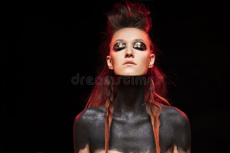 Портрет молодой изуверской девушки Нагие плечи и шея покрыты с черной краской Схематический макияж с листовым золотом на ей стоковое фото rf