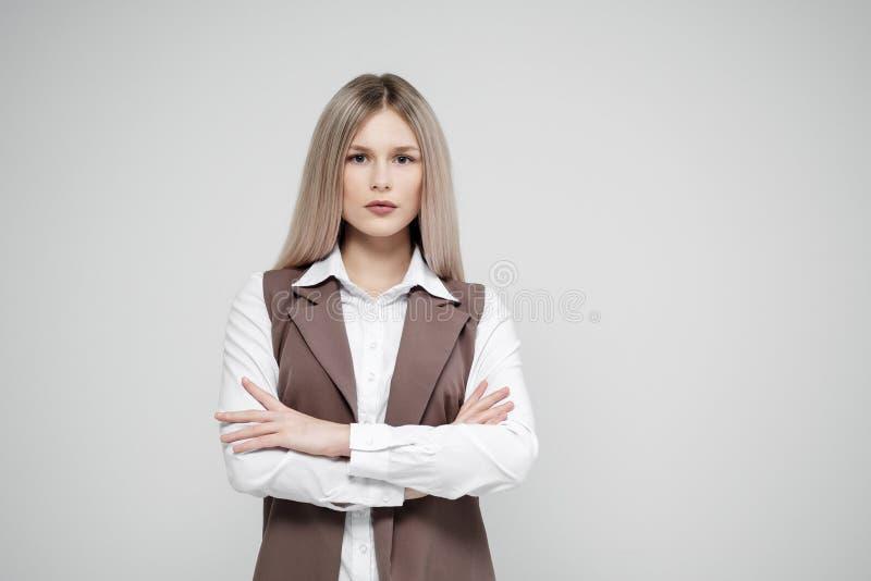Портрет молодой красивой белокурой женщины на серой предпосылке в костюме коричневого цвета дела стоковые фото