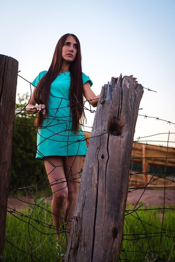 Портрет молодой красивой девушки в платье бирюзы около колючей проволоки летом на открытом воздухе стоковое изображение rf