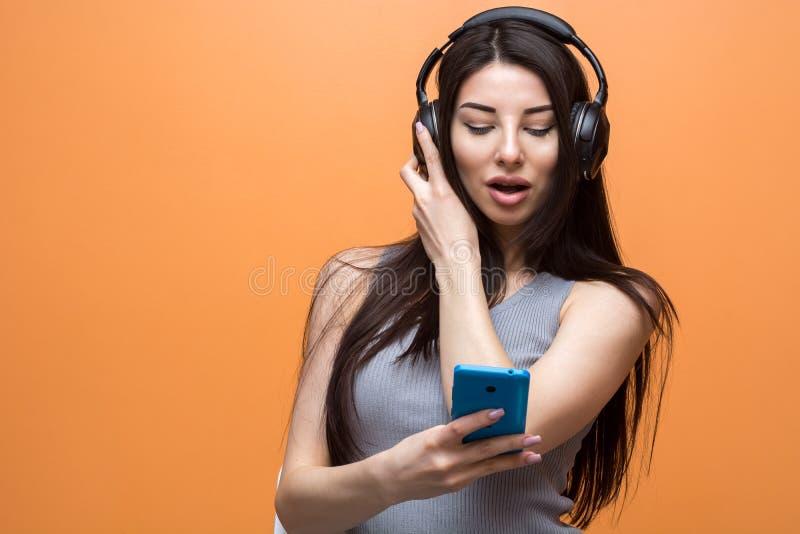 Портрет молодой красивой девушки слушая к музыке через шлемофон и смотря ее умный телефон стоковая фотография