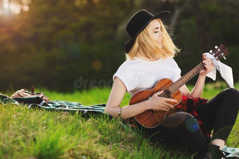 Портрет молодой красивой женщины в черной шляпе Девушка сидя на траве и играя гитару стоковые изображения