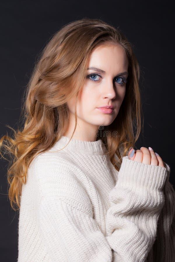 Портрет молодой, красивой женщины на черной предпосылке в большом свитере стоковые изображения