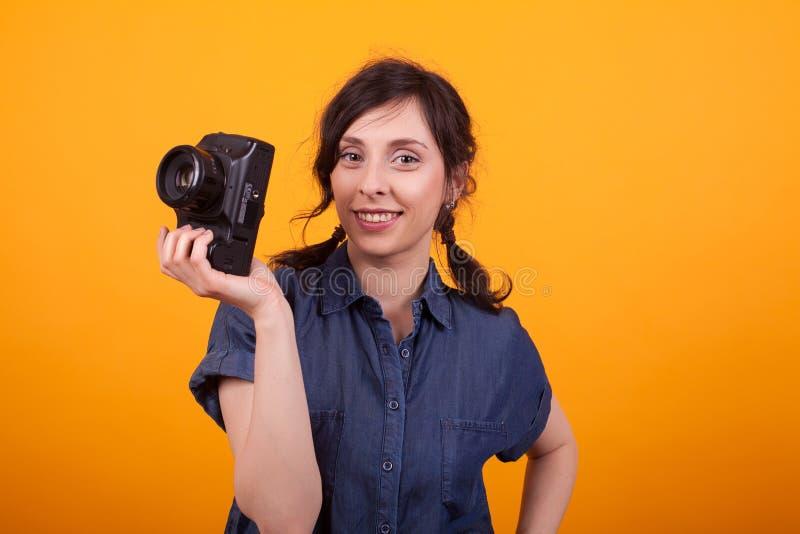 Портрет молодой красивой женщины усмехаясь на камере и держа камеру фото в студии над желтой предпосылкой стоковые фотографии rf