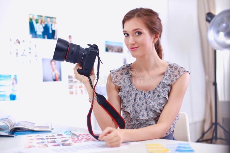 Портрет молодой красивой женщины фотографа около таблицы стоковое фото rf