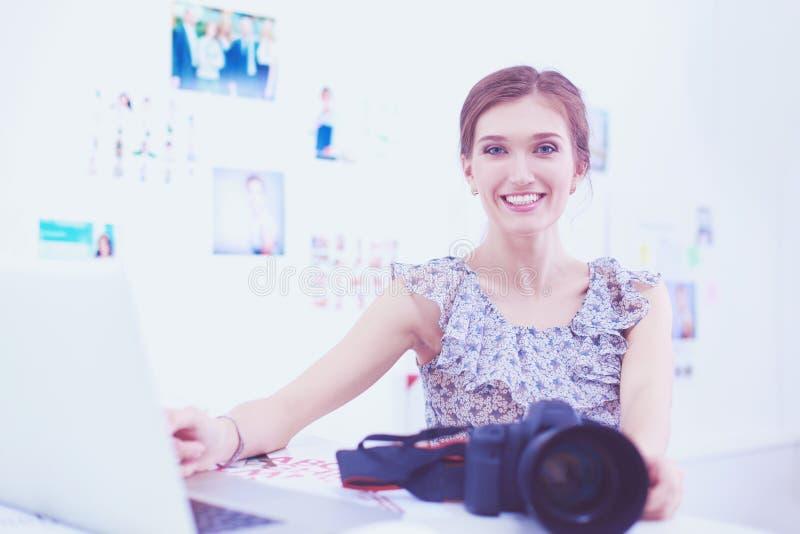 Портрет молодой красивой женщины фотографа около таблицы стоковое фото