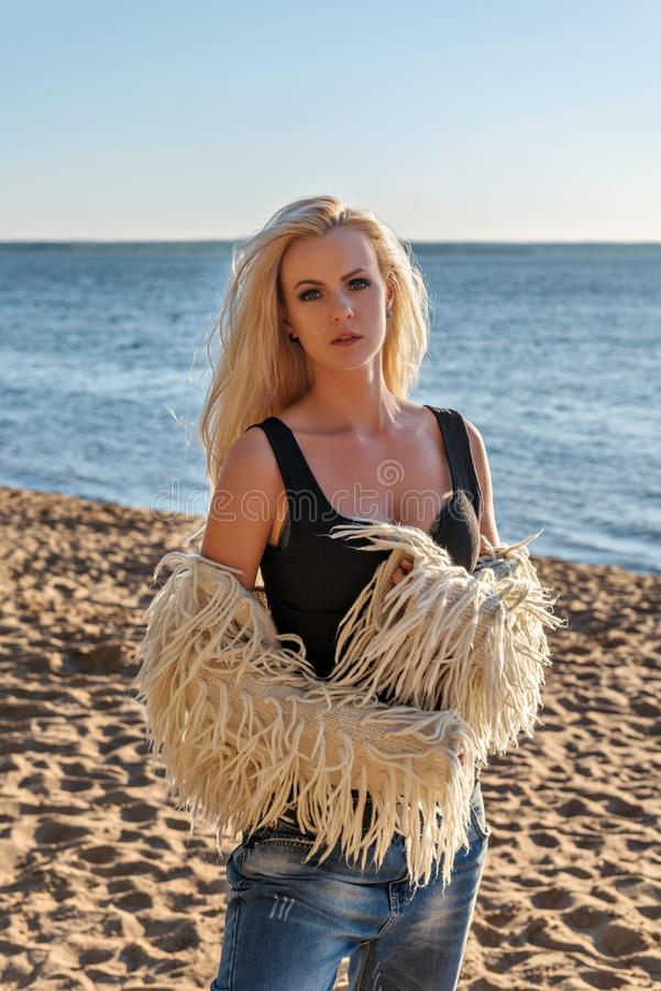 Портрет молодой красивой нежной блондинкы в джинсах с черной футболкой и белой курткой меха на песчаном пляже в лучах t стоковое фото rf