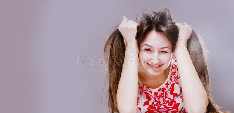 Портрет молодой красивой счастливой усмехаясь женщины играя с ее длинными волосами стоковое изображение