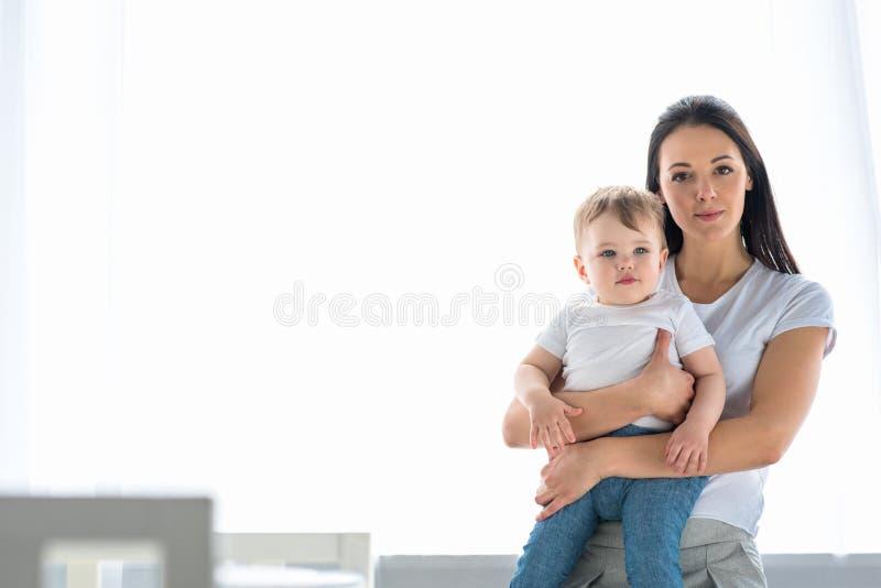портрет молодой матери держа меньшего младенца в руках стоковые фотографии rf
