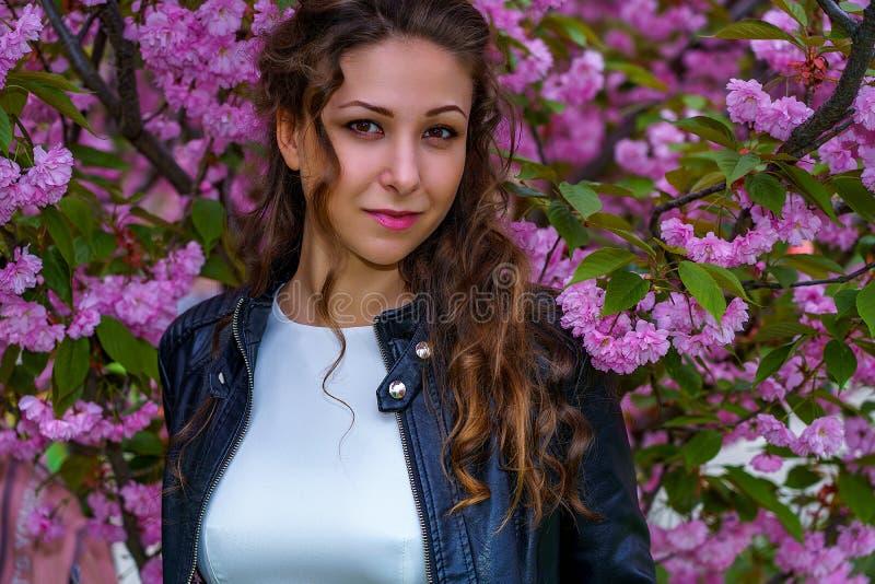 Портрет молодой милой девушки с вьющиеся волосы в белом платье и черной кожаной куртке Улыбки и взгляды женщины на камере стоковые изображения