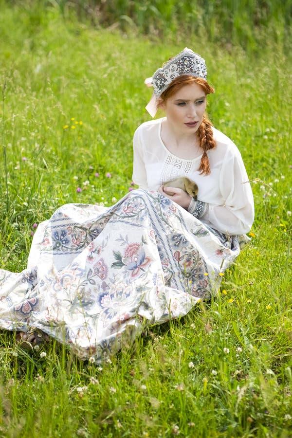 Портрет молодой нежной кавказской девушки представляя держащ утенка в русском платье стиля и Outdoors Kokoshnik стоковые изображения