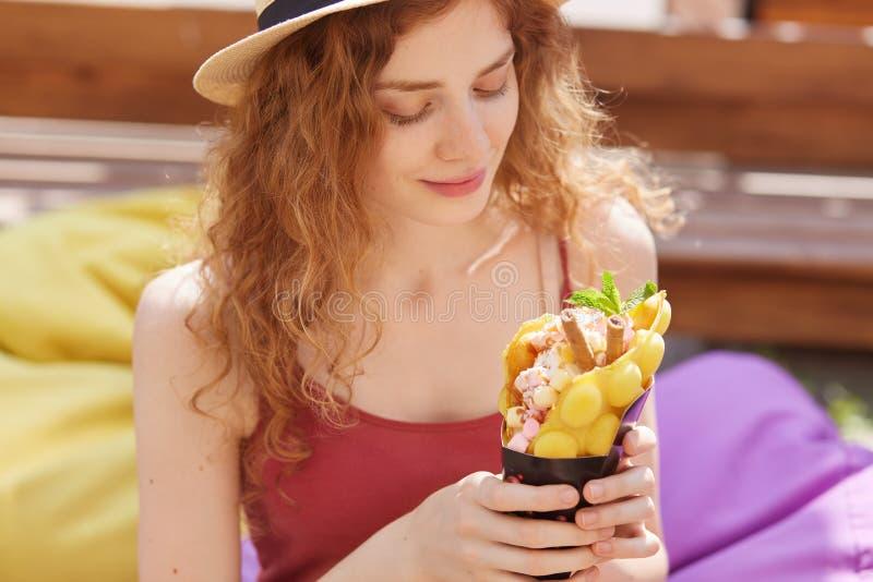 Портрет молодой прелестной женщины смотря ее десерт с наслаждением, находящся в хорошем настроении, охлаждающ вне самостоятельно, стоковая фотография rf