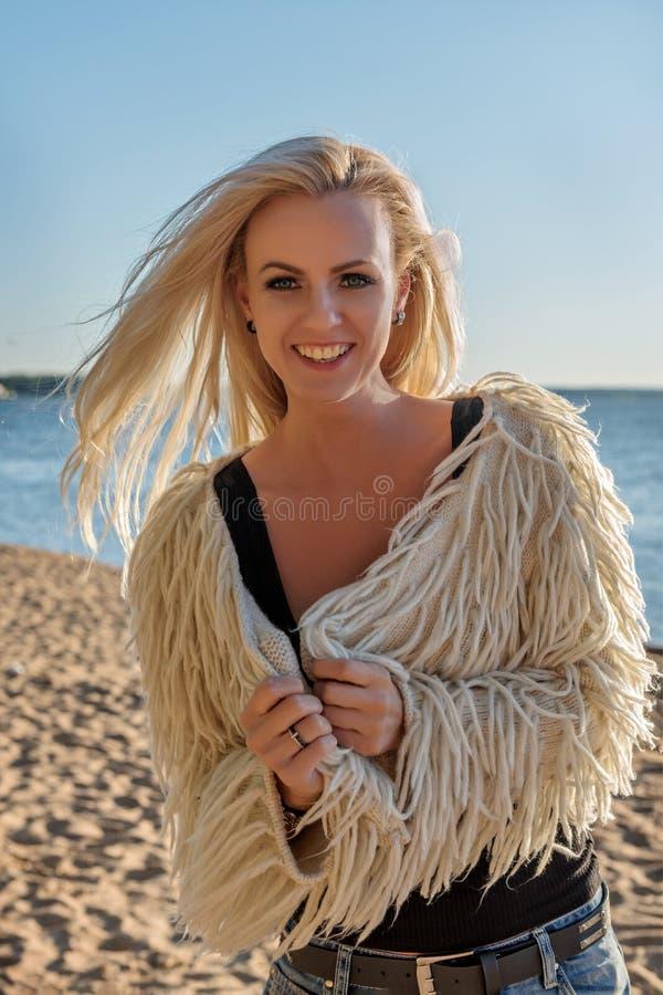 Портрет молодой привлекательной белокурой женщины усмехаясь обширно на побережье стоковое фото