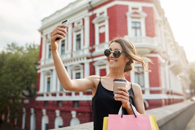 Портрет молодой привлекательной женственной кавказской девушки с темными волосами в tan стеклах и черном платье усмехаясь ярко стоковые изображения rf
