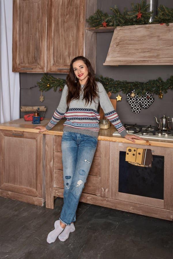 Портрет молодой привлекательной женщины брюнета на кухне украшенной Новым Годом в clothers образа жизни стоковое изображение