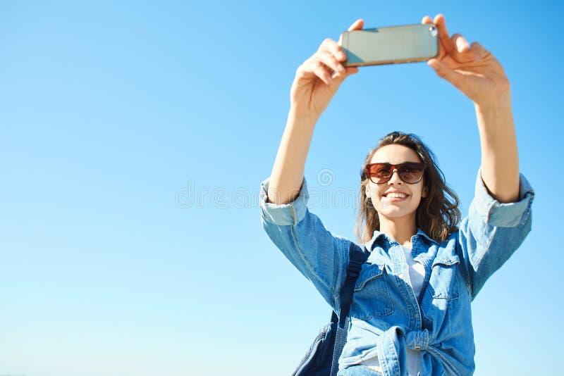Портрет молодой привлекательной женщины используя телефон на предпосылке голубого неба стоковое изображение