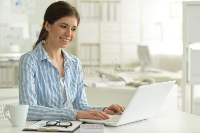 Портрет молодой привлекательной женщины работая с ноутбуком в офисе стоковая фотография