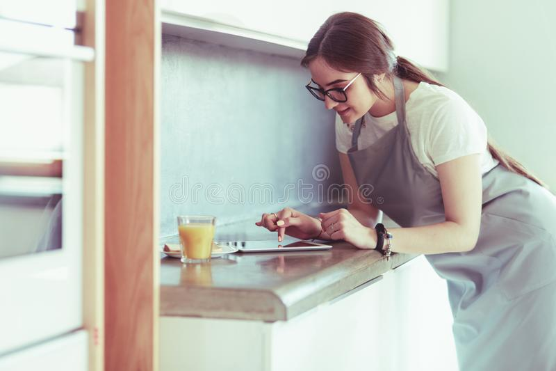 Портрет молодой привлекательной кавказской домохозяйки брюнета на кухне Утро с ПК чашки кофе и планшета стоковое изображение rf