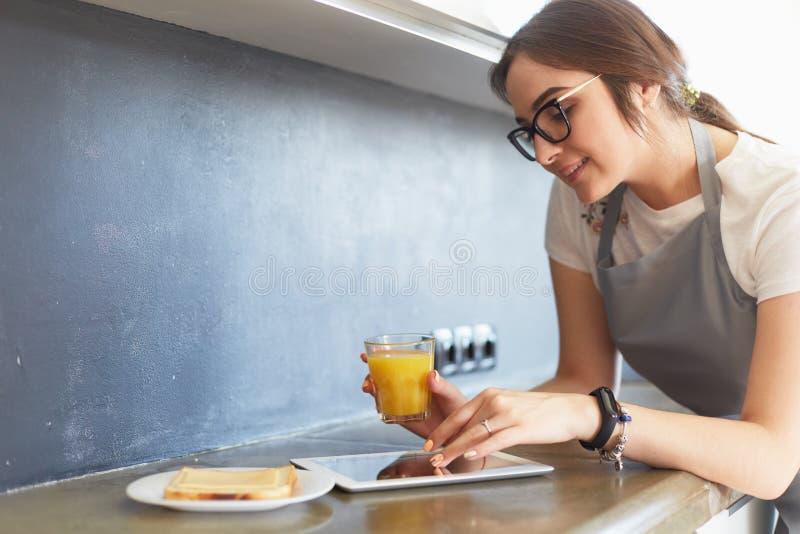 Портрет молодой привлекательной кавказской домохозяйки брюнета на кухне Утро с ПК чашки кофе и планшета стоковая фотография rf