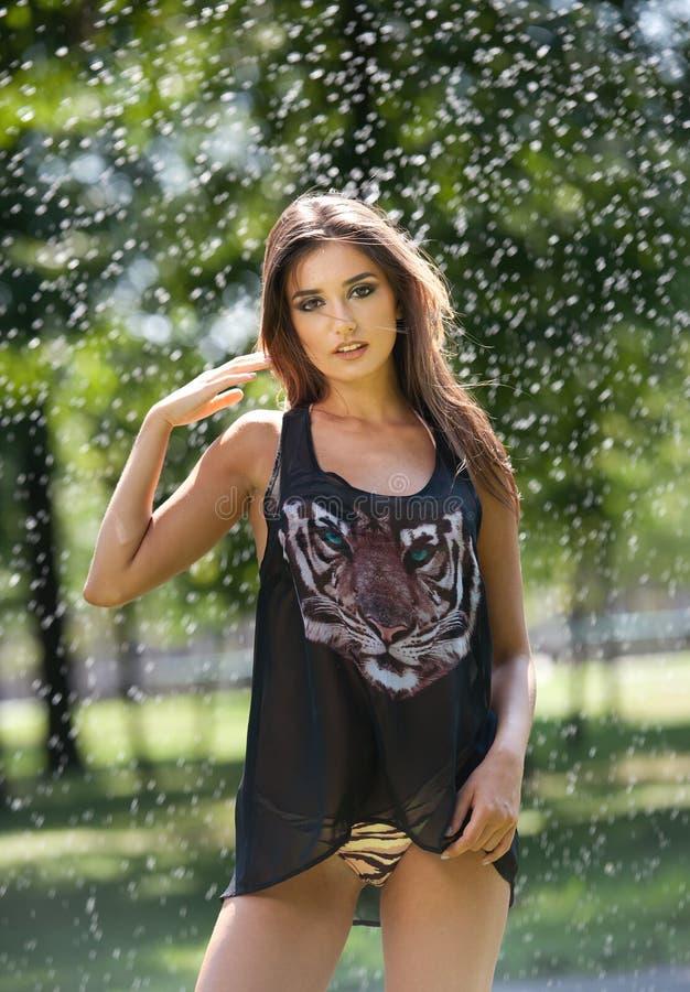 Портрет молодой сексуальной женщины в брызге воды Красивые девушки с длинными ногами и улыбками Счастливая молодая женщина в парк стоковая фотография