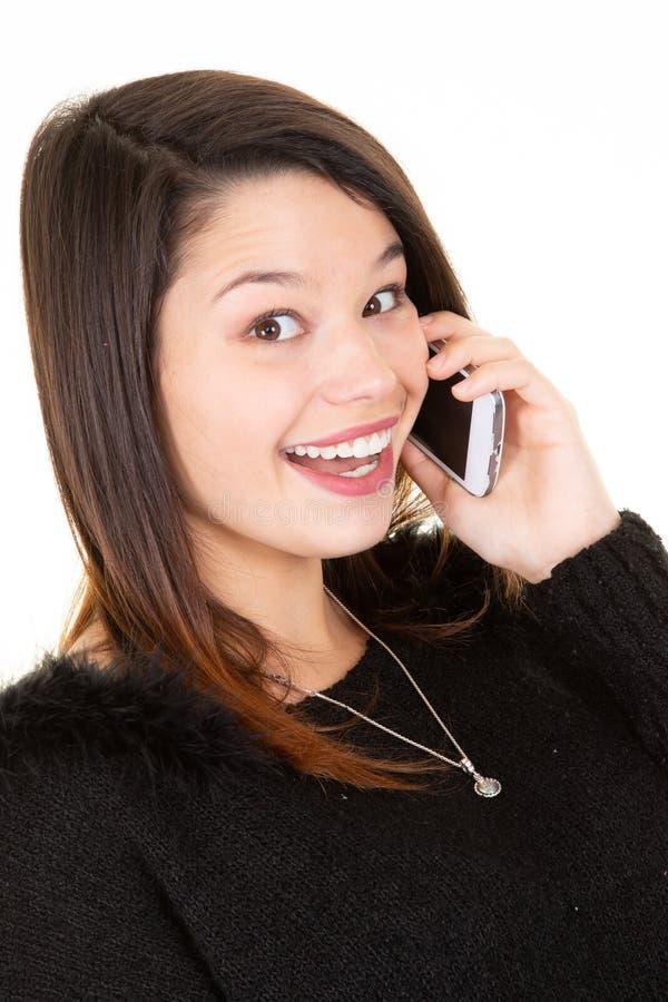 Портрет молодой счастливой женщины усмехаясь используя мобильный телефон изолированный над белой предпосылкой стоковое фото rf