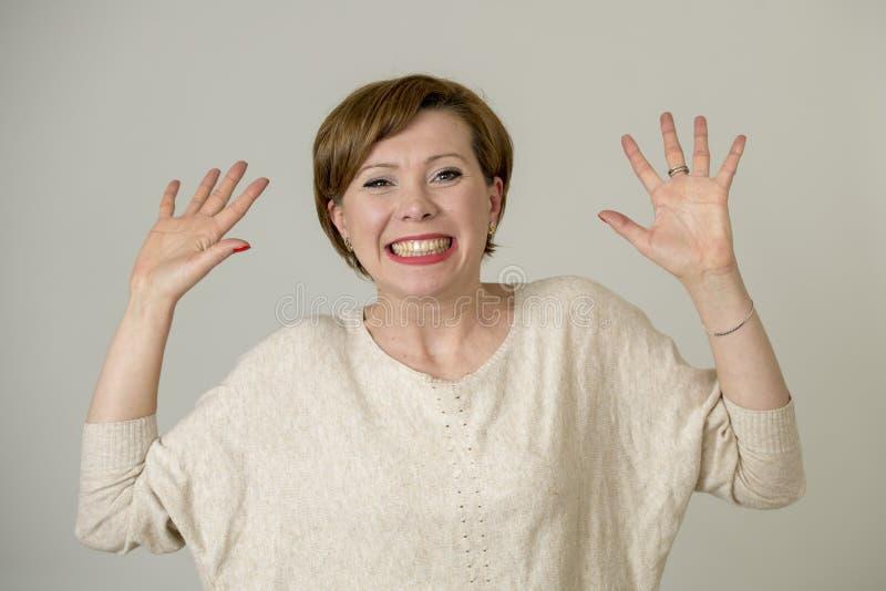 Портрет молодой счастливой и довольно красной женщины волос на ее 30s в сладостной улыбке возбудил представлять с руками вверх по стоковая фотография