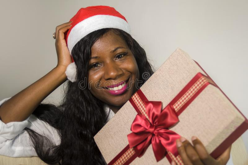 Портрет молодой счастливой и красивой черной Афро-американской женщины в шляпе Санта Клауса держа присутствующий усмехаться короб стоковое фото