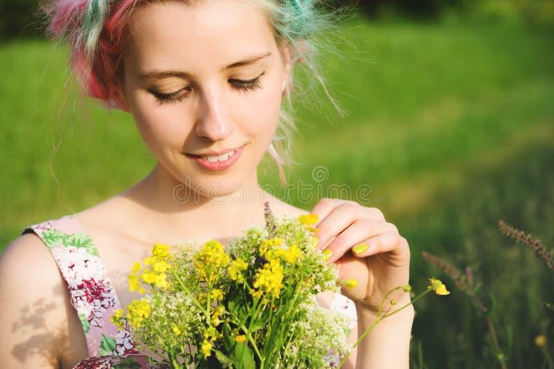 Портрет молодой счастливой усмехаясь девушки в платье хлопка с букетом wildflowers стоковые изображения