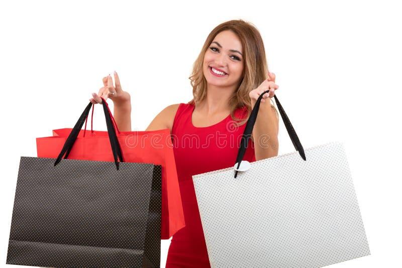 Портрет молодой счастливой усмехаясь женщины с хозяйственными сумками, изолированный над белой предпосылкой стоковое фото