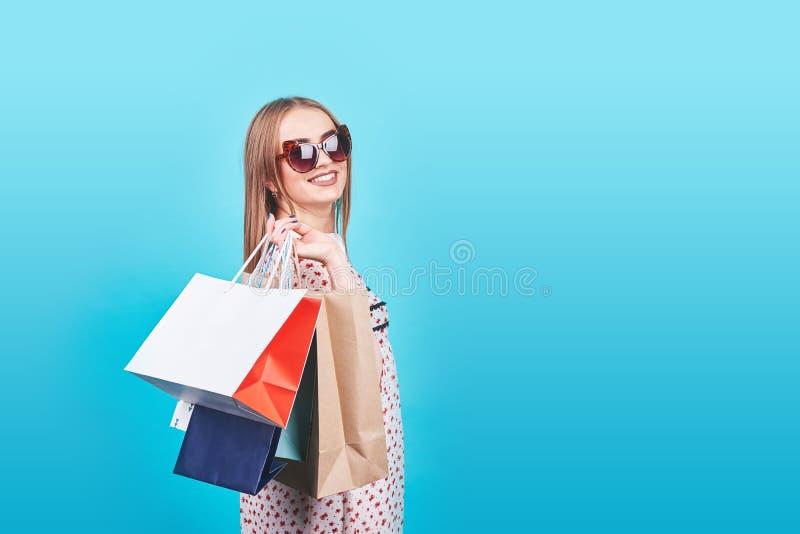 Портрет молодой счастливой усмехаясь женщины с хозяйственными сумками на голубой предпосылке стоковое изображение rf