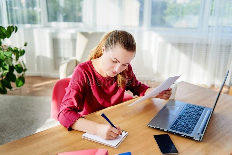 Портрет молодой уверенной бизнес-леди сидя на деревянном столе и писать план в тетради в современном офисе, космосе экземпляра стоковое изображение