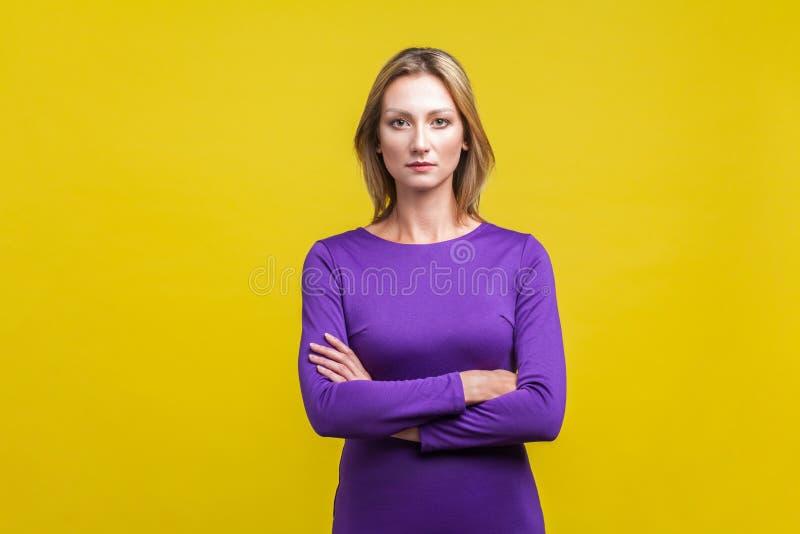 Портрет молодой уверенной в себе бизнес-женщины, стоящей с пересеченными руками изолированный от желтого фона стоковая фотография rf