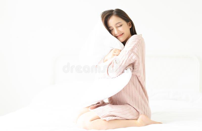 Портрет молодой усмехаясь азиатской девушки в пинке свитера обнимая подушку сидя в кровати на ее спальне Доброе утро, новый день, стоковое фото rf