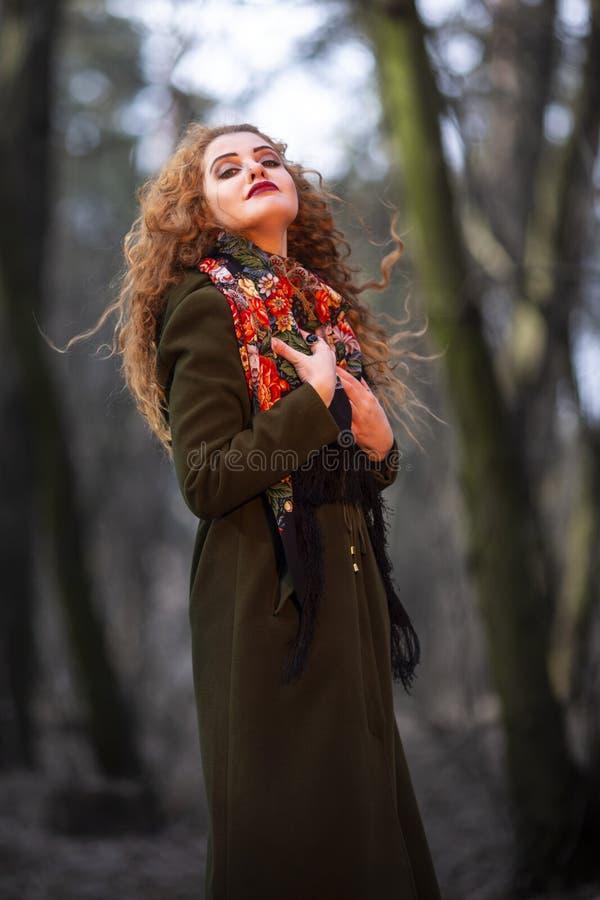 Портрет молодой усмехаясь кавказской женщины с красными волосами представляя в Outdoors леса стоковое изображение rf