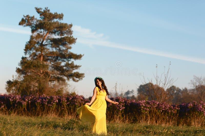 Портрет молодой усмехаясь красивой женщины в желтом платье на пурпурном поле луга цветения цветка outdoors на backgrou природы ле стоковое фото rf