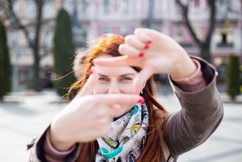 Портрет молодой усмехаясь привлекательной женщины redhead на весеннем дне на предпосылке города женщина показывает рамку от стоковая фотография rf