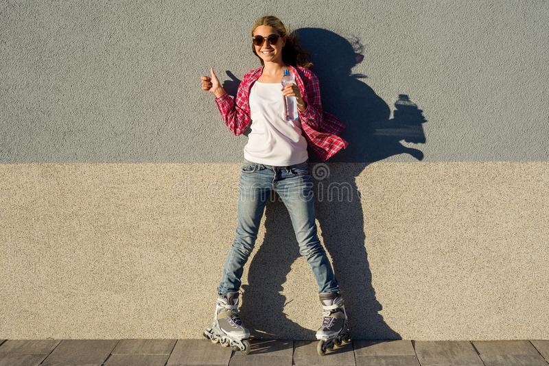 Портрет молодой холодной усмехаясь девушки обутой в rollerblades, holdin стоковая фотография